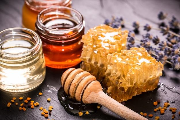 Honey in jar with honey dipper on black stone Premium Photo