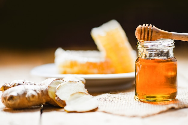 Honey in jar with honey dipper ginger and on wood and honeycomb Premium Photo