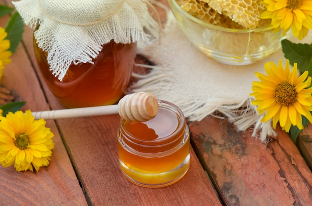 Honey in jar with honey dipper on rustic wooden table Premium Photo