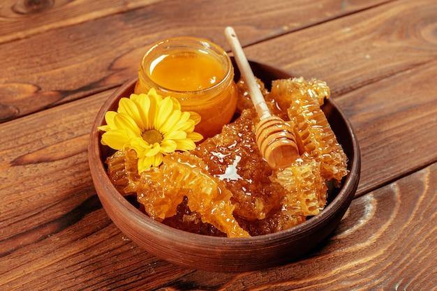 Honey in jar with honey dipper on vintage wooden background Premium Photo