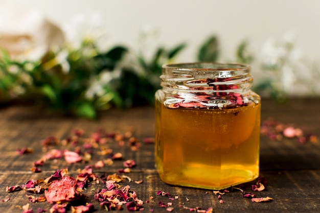 Honey jar with petals Free Photo