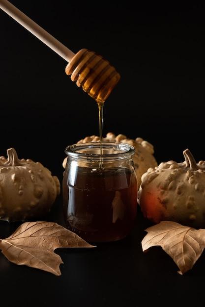 Баночка меда с ложкой с тыквами и осенними листьями Premium Фотографии