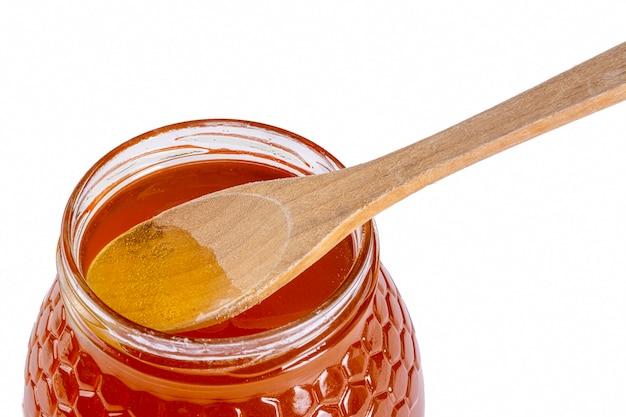 Barattolo di miele con cucchiaio di legno Foto Gratuite