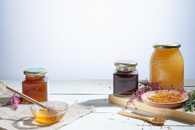 Медовые баночки с медовыми палочками и цветами Premium Фотографии