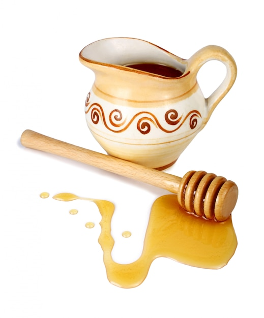 Honey in a jug and wooden stick Premium Photo