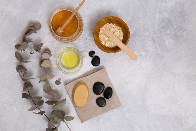 Honey; oats; oil; soap and la stone on napkin with dried eucalyptus populus leaves on concrete backdrop Free Photo