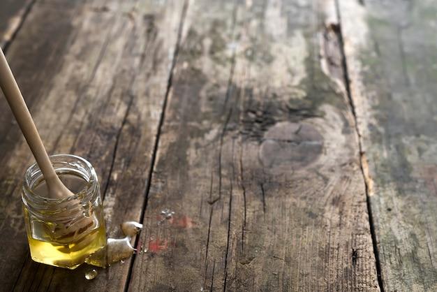 Мед органический в банке с деревянной палочкой на старом деревянном фоне Premium Фотографии