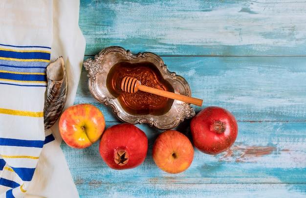 Honey on the pomegranate and apples. jewish new year yom kippur and rosh hashanah kippah yamolka and shofar Premium Photo