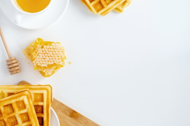 Honey products composition. honeycomb, waffles, tea and special spoon. white background Free Photo