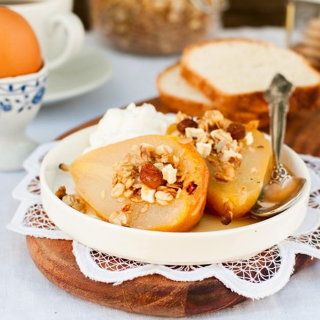 Honey roast pears with granola and yogurt Premium Photo