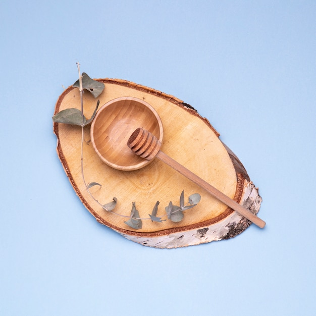 Honey spoon with wooden bowl on blue background Free Photo