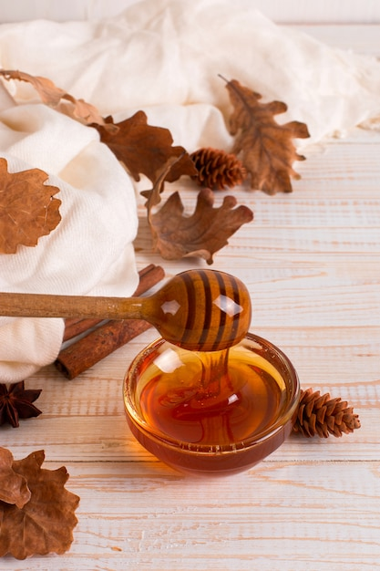 Honey, stick, jar, scarf, dry leaves. rustic sweet autumn photo, white wooden background, copyspace. Premium Photo