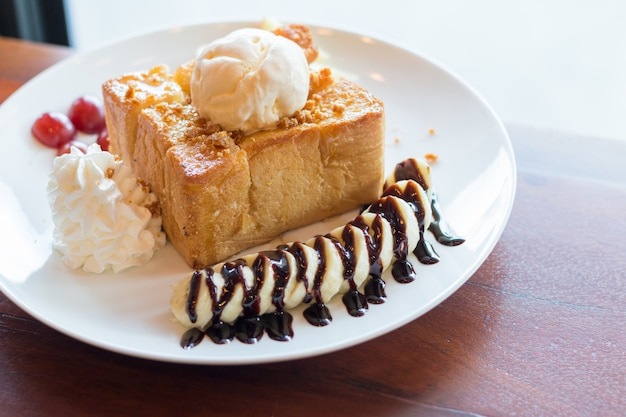 Honey toast with vanilla ice cream, whipped cream and chocolate syrup. served with banana, grape and apple Premium Photo
