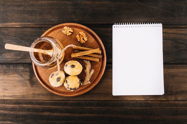 Honey; walnut; spices and cup cakes near spiral notepad on wooden surface Free Photo