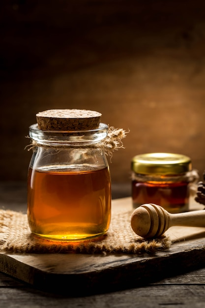 Honey with dipper on wooden background Premium Photo