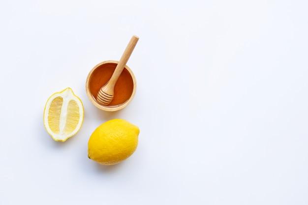 Honey with lemon on white background Premium Photo