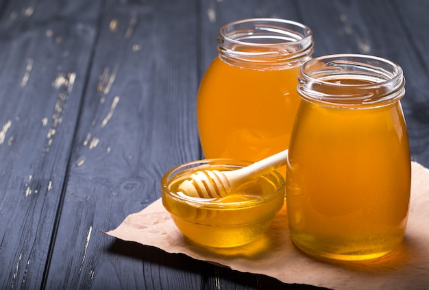 Honey with wooden honey dipper on wooden table Premium Photo