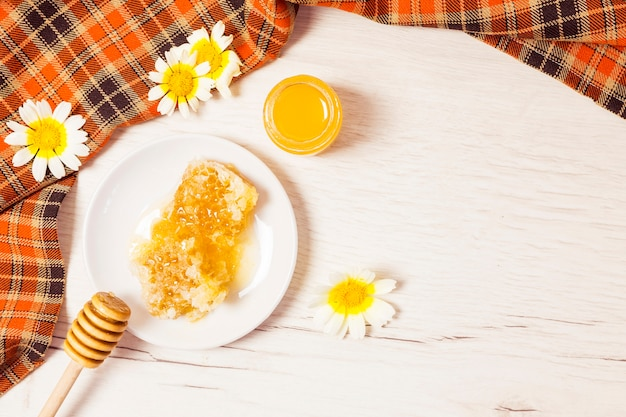 Honeycomb and honey with checkered table cloth on wooden desk Free Photo