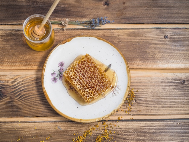Honeycomb piece on white plate with honey pot over the wooden table Free Photo