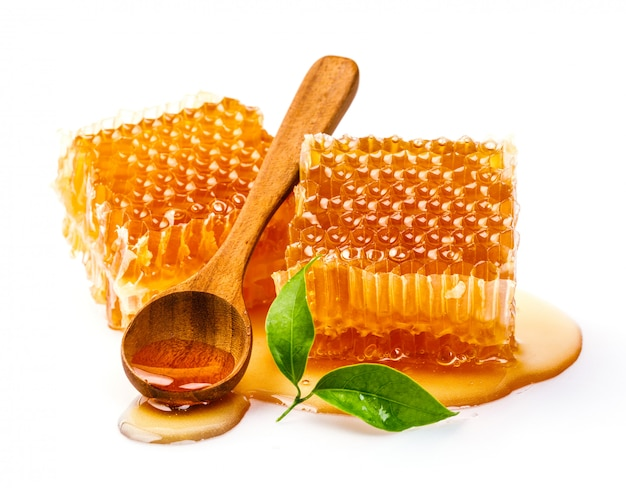 Honeycomb with honey spoon and leaf isolated on white background Premium Photo