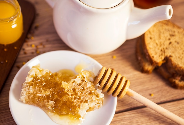 Honeycomb with tea and bread on table Free Photo