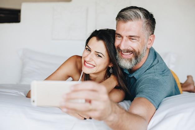 Honeymooners taking a selfie in bed Premium Photo