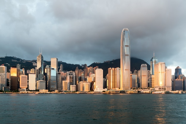 Hong kong skyline with sunlight in the morning over victoria harbour in hong kong. Premium Photo