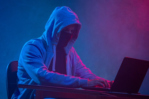 Hooded computer hacker stealing information with laptop Free Photo