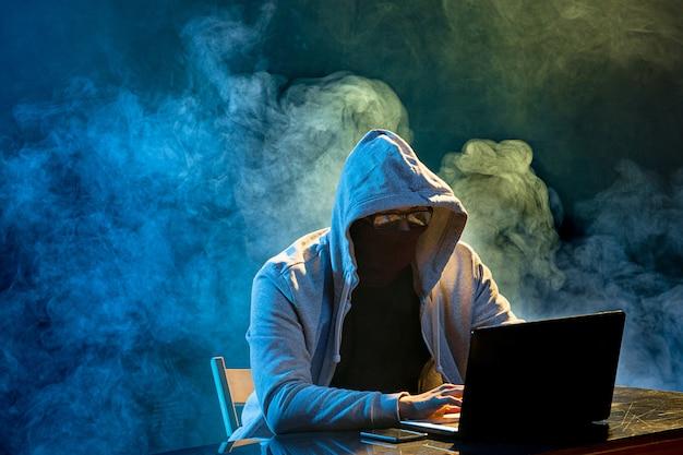 Hacker komputer berkerudung mencuri informasi dengan laptop Free Photo