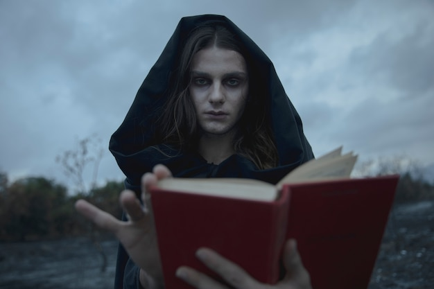Hooded man looking at camera with blurred book Free Photo