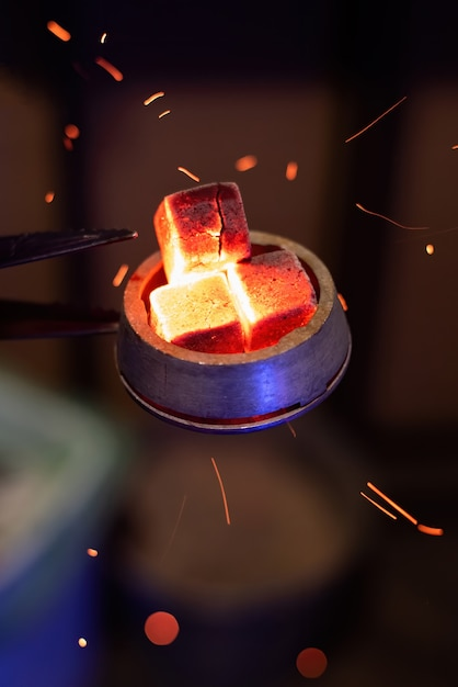 Hookah bowl with heated coals on it, particles flying around Free Photo