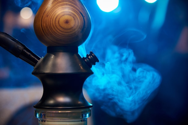 Hookah close-up in the smoke on a blue background Premium Photo