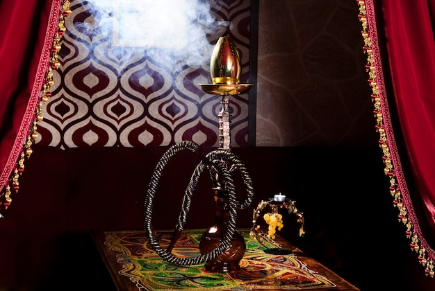 Hookah on a dark background of a blurry bar with a bokeh.copy space Premium Photo