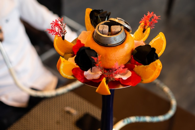 Hookah decorated with orange, black roses and other flowers Free Photo
