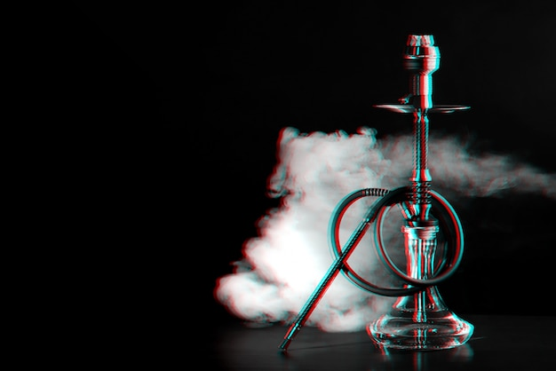Hookah with coals and smoke on the table in a restaurant Premium Photo