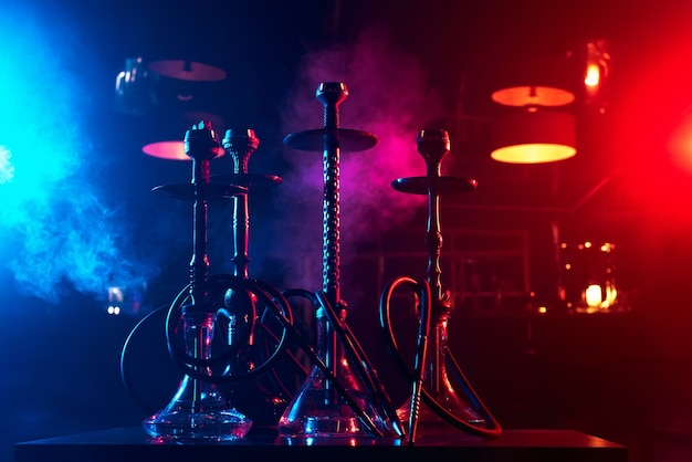 Hookahs on the table with smoke and red and blue light in the lounge cafe. concept of traditional eastern arabic relaxing with a shisha Premium Photo