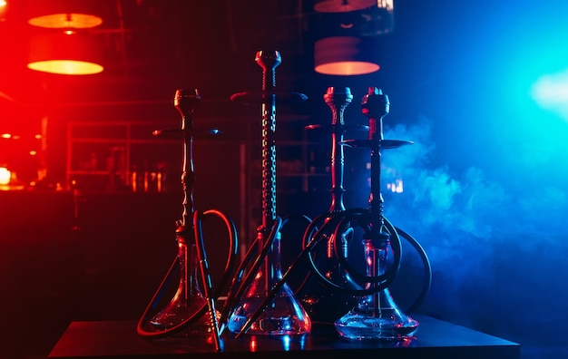 Hookahs with shisha bowls and coals on the background of smoke in the restaurant for relaxation with tobacco use Premium Photo