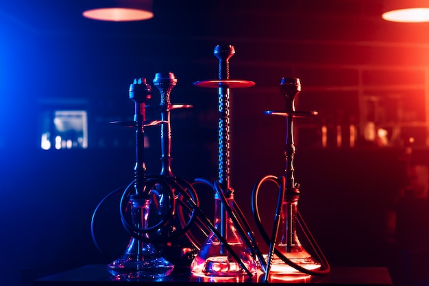 Hookahs with shisha charcoals in bowls on the table in the restaurant for traditional arabic relaxation Premium Photo