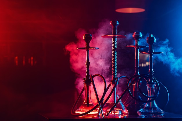 Hookahs with shisha coals in bowls against a background of smoke with neon lighting in a restaurant with a copy space Premium Photo