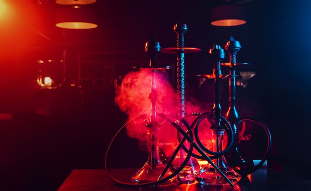 Hookahs with shisha glass flasks and metal bowls with coals for relaxation Premium Photo