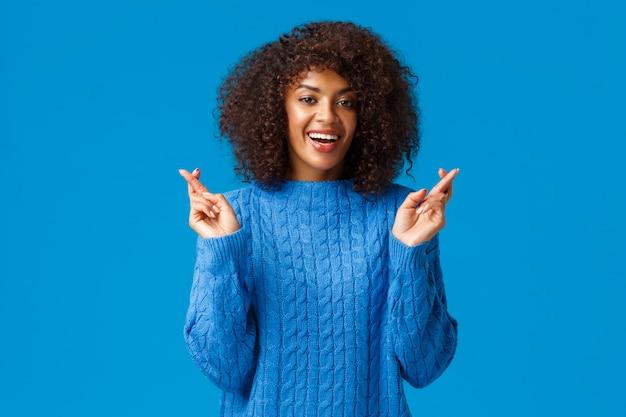 Надеюсь, мои новогодние пожелания сбудутся. веселая, обнадеживающая и оптимистичная красивая афроамериканка в зимнем свитере, скрестив пальцы на удачу и взволнованная улыбка, предвкушая мечту Premium Фотографии