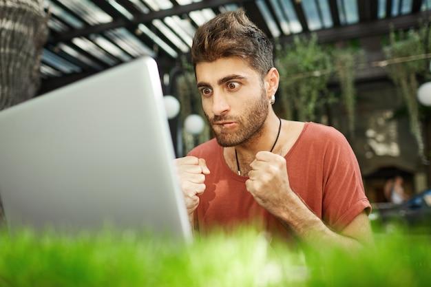 Обнадеживающий и напряженный красивый программист сжимает кулаки и с нетерпением смотрит на экран ноутбука, программа тестирования Бесплатные Фотографии