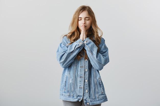 Promettente ragazza bionda in giacca di jeans che esprime desiderio, tenendosi per mano in supplica, pregando Foto Gratuite