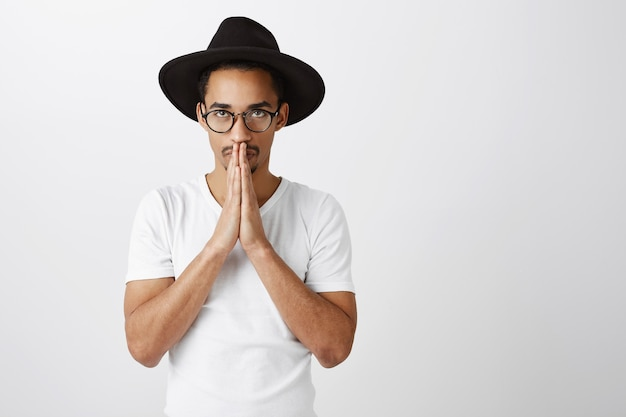 Обнадеживающий красивый афро-американский молодой человек, взявшись за руки в молитве, умоляя или прося, пожалуйста Бесплатные Фотографии