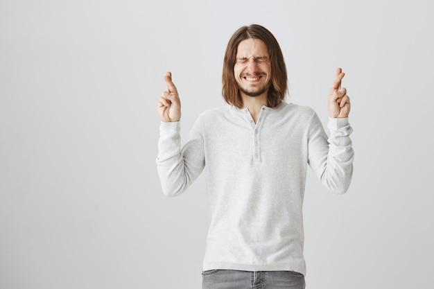 希望に満ちた笑顔と楽観的な男のクロスフィンガー幸運 無料写真
