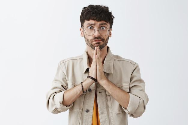 Hopeful stylish bearded guy posing against the white wall Free Photo