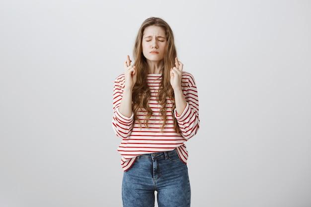 Обнадеживающая взволнованная девушка скрестит пальцы удачи, закроет глаза и молится, загадывая желание Бесплатные Фотографии
