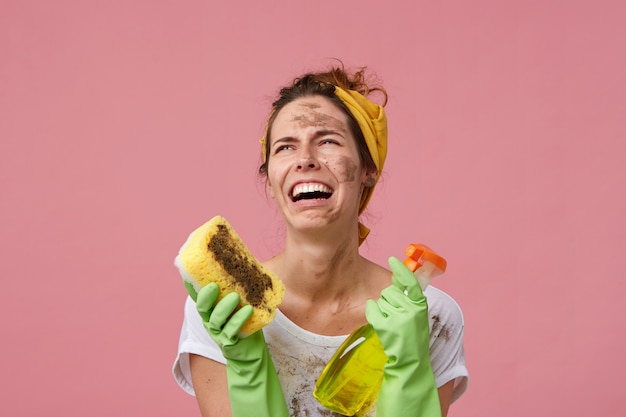 Безнадежная плачущая домохозяйка с грязной одеждой и лицом в повседневной одежде и перчатках с губкой и моющим средством в руках устала от уборки. у молодой горничной много работы Бесплатные Фотографии
