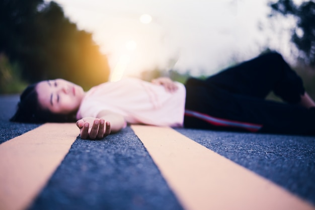 Hopeless girl lying down on street at sunset Premium Photo