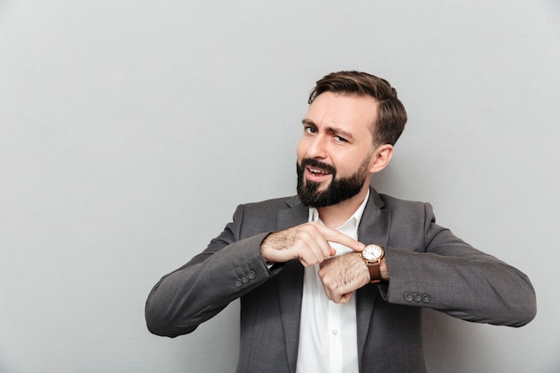 Horizontal bearded man pointing at his wrist watch, posing isolated over gray Free Photo